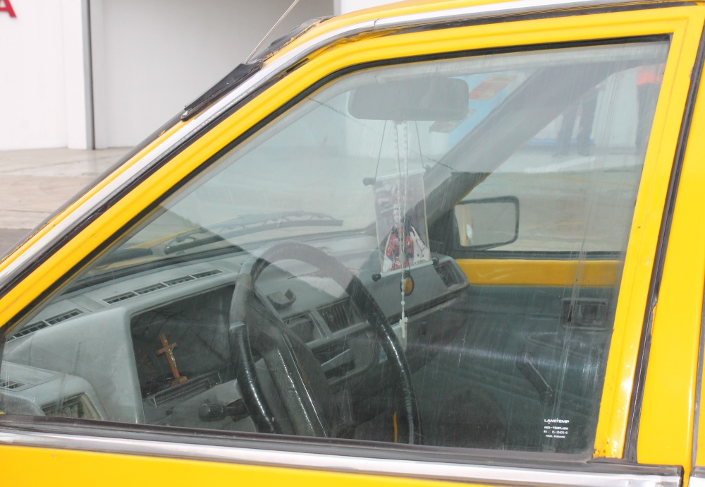 A Catholic banner and crucifix hang from the mirror of an independent cab in Miraflores (photo: Alex Pashley)