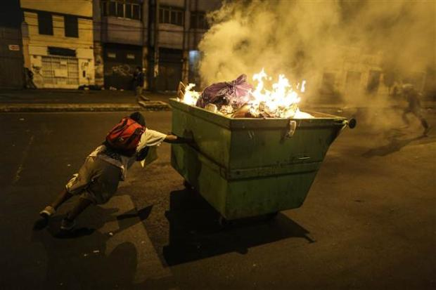 A protestor pushes a blazing trash can in downtown Lima. Police made 20 arrests (photo: Anadolu Agency)